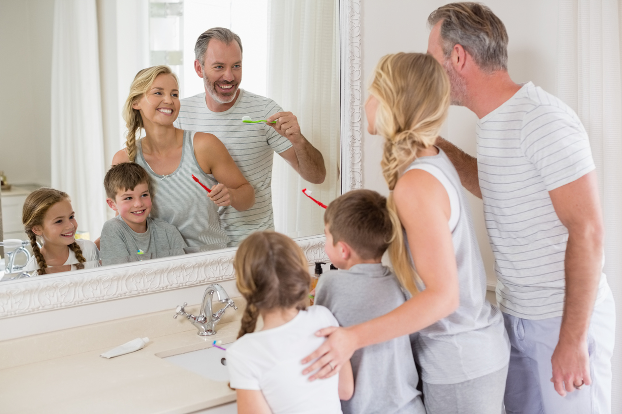 Parents and kids brushing teeth in bathroom