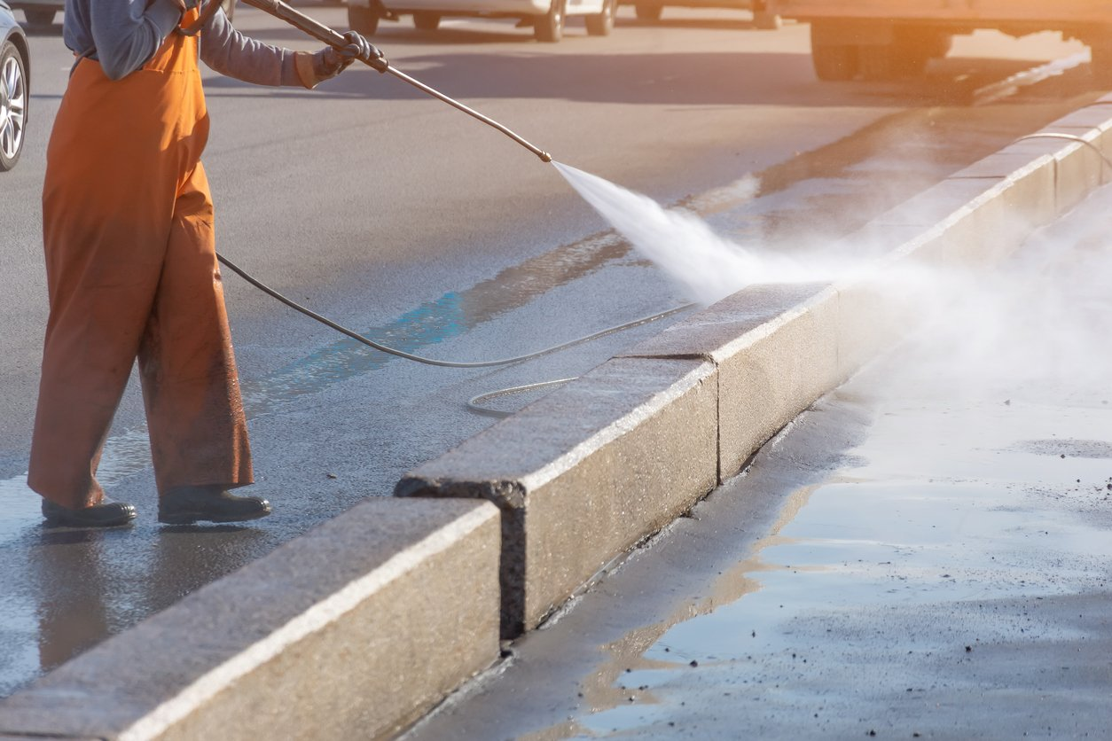 Worker cleaning driveway with gasoline high pressure washer splashing the dirt, asphalt road border. High pressure cleaning.